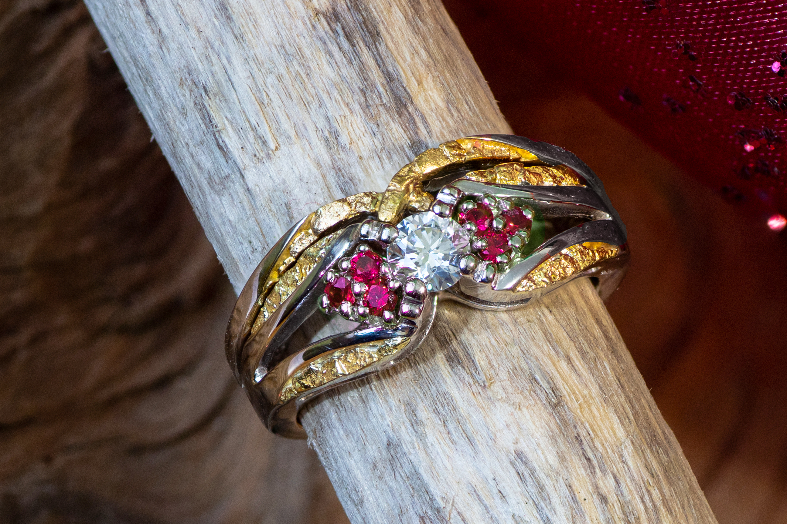 Stunning diamond center stone surrounded with gorgeous Alaskan gold nuggets and Rubies fancily arranged in 14kt white gold.